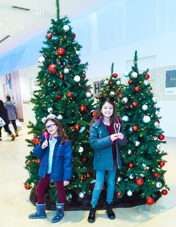 Sisters standing with candy canes in front of decorated Christmas Trees: tania2atee